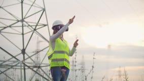 Женский инженер управляет передачей альтернативной энергии от панелей солнечных батарей и ветровых электростанций к потребителям  акции видеоматериалы