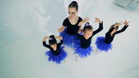 Женский инструктор помогает маленьким балеринам держать позицию видеоматериал
