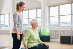 Женский инструктор помогая старшей женщине работая в спортзале Стоковая Фотография RF