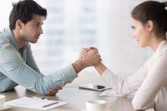 Женский и мужской armwrestling соперников дела, состязаясь для руководства Стоковые Изображения RF