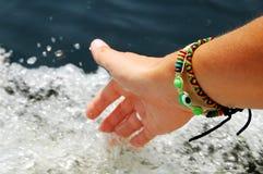 Женский касаться руки брызгает пенясь воды пока плавающ на шлюпке двигателя Стоковая Фотография RF