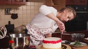 Женский кашевар застекляет торт видеоматериал
