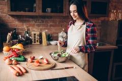 Женский кашевар, салат варя на кухне Стоковая Фотография