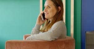 Женский клиент говоря на мобильном телефоне в магазине 4k бутика акции видеоматериалы