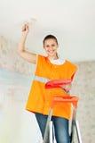 Женский колеривщик дома красит потолок Стоковое Изображение