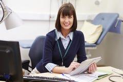 Женский консультант используя таблетку цифров на столе в офисе стоковое фото rf