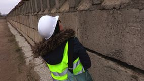 Женский контролер проверяя и идя около бетонной стены акции видеоматериалы