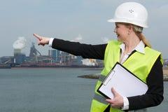 Женский контролер в защитном шлеме и безопасность возлагают указывать на промышленное место Стоковая Фотография