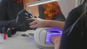 Женский красный цвет делает процедуру по курорта для ногтей клиента видеоматериал