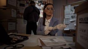 Женский криминолог кладя на перчатки для того чтобы рассмотреть доказательство, професиональные квалификации стоковое изображение rf