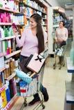 Женский клиент выбирая продукты аптеки Стоковое фото RF
