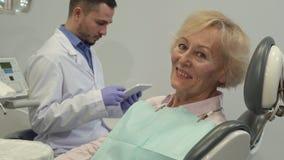 Женский клиент показывает ее большой палец руки вверх на зубоврачебном стуле видеоматериал