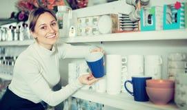 Женский клиент рассматривает чашки Стоковое Фото