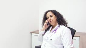 Женский латинский женский доктор сидя смотрящ на камеру в ее кабинете врача со стетоскопом на ее шеи говоря с ее смартфоном стоковая фотография