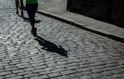 Женский марафонец и ее тень на улице города cobblestoned Стоковое Фото