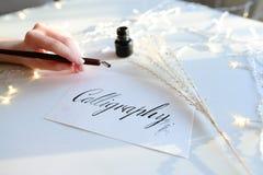 Женский мастер литерности чернил пишет слово на бумаге, усаживание Стоковое Изображение RF