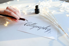 Женский мастер литерности чернил пишет слово на бумаге, усаживание Стоковое фото RF