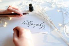Женский мастер литерности чернил пишет слово на бумаге, усаживание Стоковое Изображение