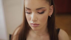 Женский мастер макияжа использует щетку порошка Красивая модель в студии красоты Профессионал составляет моду финиша художника сток-видео