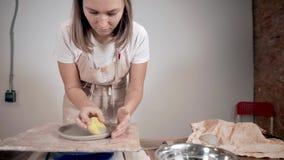 Женский мастер формирует края керамической плиты, поворачивая его на  видеоматериал