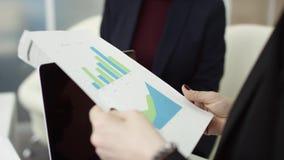 Женский менеджер представляет новый план проекта к коллегам на встрече, объясняя идеи на бумагах сотрудникам в офисе видеоматериал