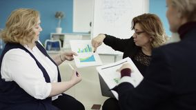 Женский менеджер представляет новый план проекта к коллегам на встрече, объясняя идеи на orkers бумаг, коммерсантка сток-видео