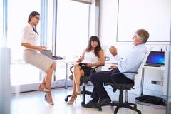 Женский менеджер говоря к коллегам в современном офисе Стоковые Фото
