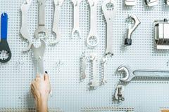Женский механик выбирая ключ гайки в мастерской Стоковые Фото