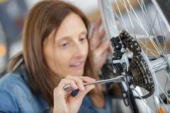 Женский механик затягивая педаль на велосипеде стоковые изображения