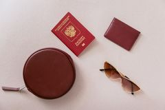 Женский минимальный набор перемещения Maroon паспорт, владелец карточки и бумажник с сумкой и стекла на пастельной бежевой предпо стоковое фото