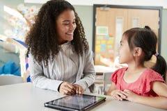 Женский младенческий школьный учитель работая одно на одном с китайской школьницей, сидя на таблице в классе используя comput пла стоковое фото