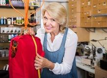 Женский модельер подшивая новые одежды на манекене стоковые изображения