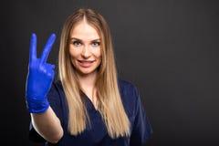 Женский носить дантиста scrubs показывать показывающ номер два стоковое изображение