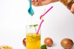 Женский добавляя мед в фруктовом соке маракуйи стоковые фотографии rf