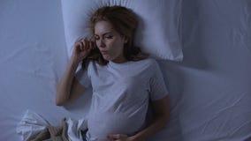 Женский ожидающий лежать в тошноте чувства кровати, болезни утра, здоровье беременности акции видеоматериалы
