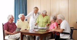 Женский доктор взаимодействуя с пожилыми гражданинами сток-видео