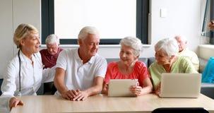 Женский доктор взаимодействуя с пожилыми гражданинами акции видеоматериалы