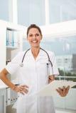 Женский доктор держа доску сзажимом для бумаги в медицинском офисе Стоковое Изображение