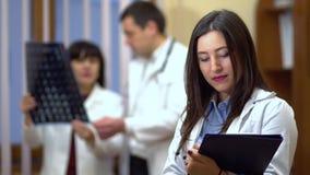 Женский доктор держа папку в его руках На заднем плане, доктора проверили рентгеновские снимки видеоматериал