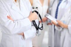 Женский доктор держа стетоскоп в его руке, 2 доктора и пациент на предпосылке Стоковые Изображения RF
