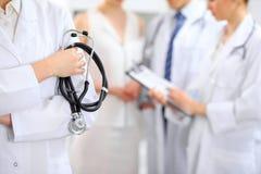 Женский доктор держа стетоскоп в его руке, 2 доктора и пациент на предпосылке Стоковое Изображение RF