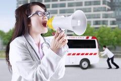 Женский доктор крича с мегафоном Стоковые Изображения