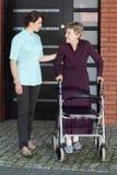 Женский доктор помогая старухе с ходоком Стоковые Фото
