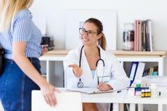 Женский доктор получая ее пациента в офисе Стоковая Фотография RF