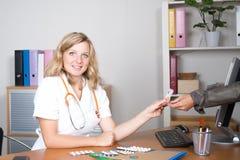 Женский доктор получая деньги от ее женского пациента Стоковое Фото