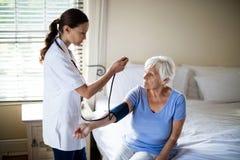 Женский доктор проверяя кровяное давление старшей женщины в спальне Стоковая Фотография RF