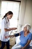 Женский доктор проверяя кровяное давление старшей женщины в спальне Стоковое фото RF