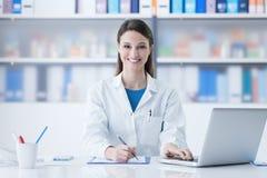 Женский доктор работая на столе офиса стоковая фотография rf