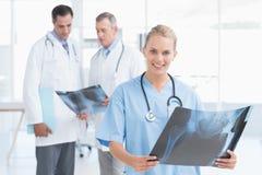Женский доктор смотря камеру пока ее коллеги работают Стоковое фото RF
