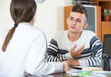 Женский доктор спрашивая предназначенного для подростков пациента на офисе Стоковое фото RF